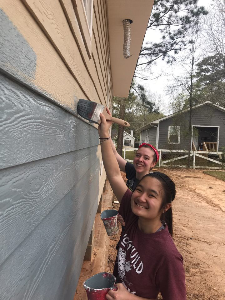 Two students smile while painting a house during Alternative Spring Break 2018