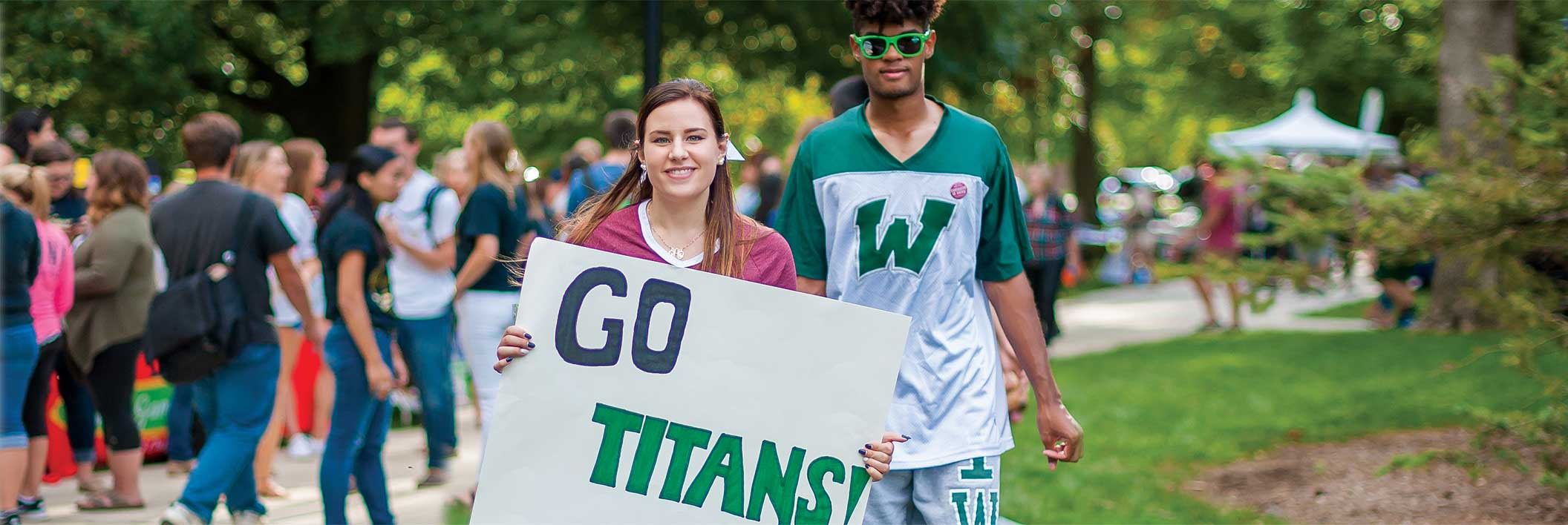 "Student smiling and holding ""Go Titans!"" sign"